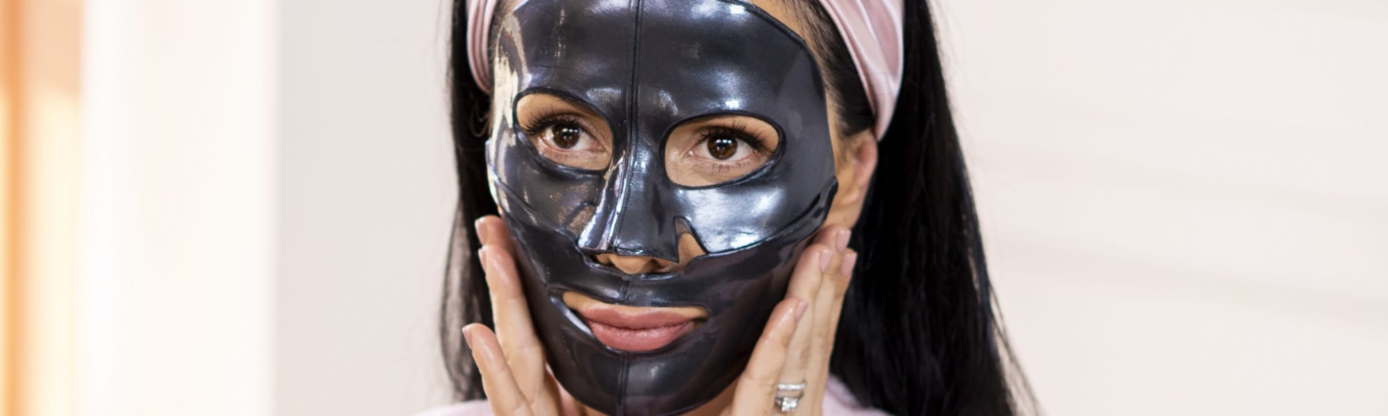 woman putting on charcoal face mask