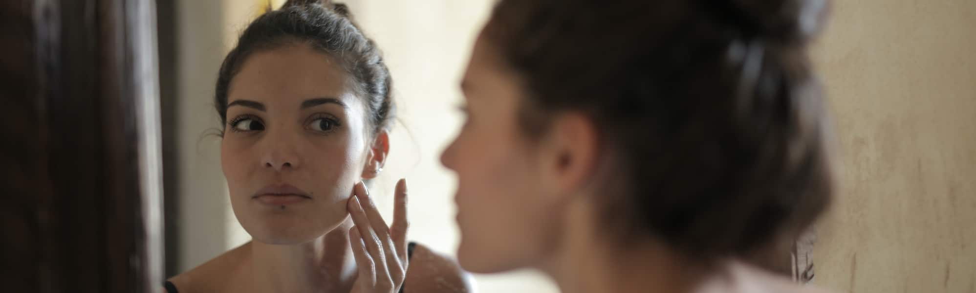 woman checking skin in the mirror